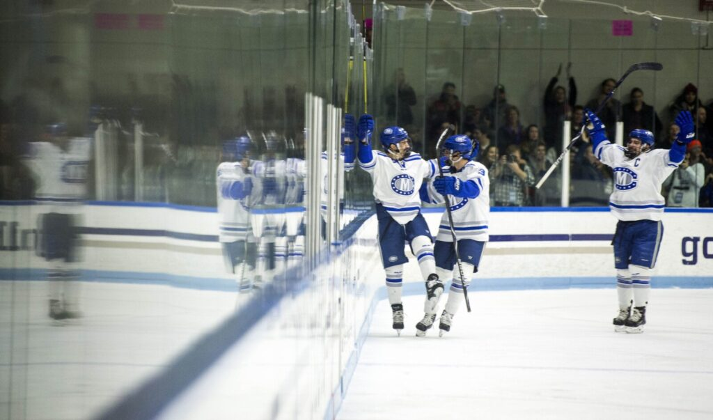 Colby's Kienan Scott, center, celebrates a first period goal against Bowdoin College in Waterville in November. The Mules have only two league wins this season.