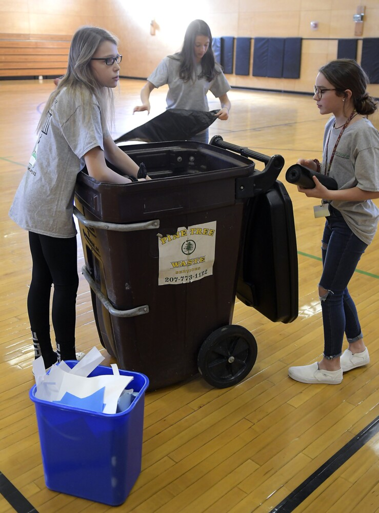 Maranacook Community Middle School students Tilden Tinkham, left, Natalie Mohlar and Mya St. Pierre recycle paper Nov. 25 at the Readfield school's gym. The crew volunteer with the school's Green Team.