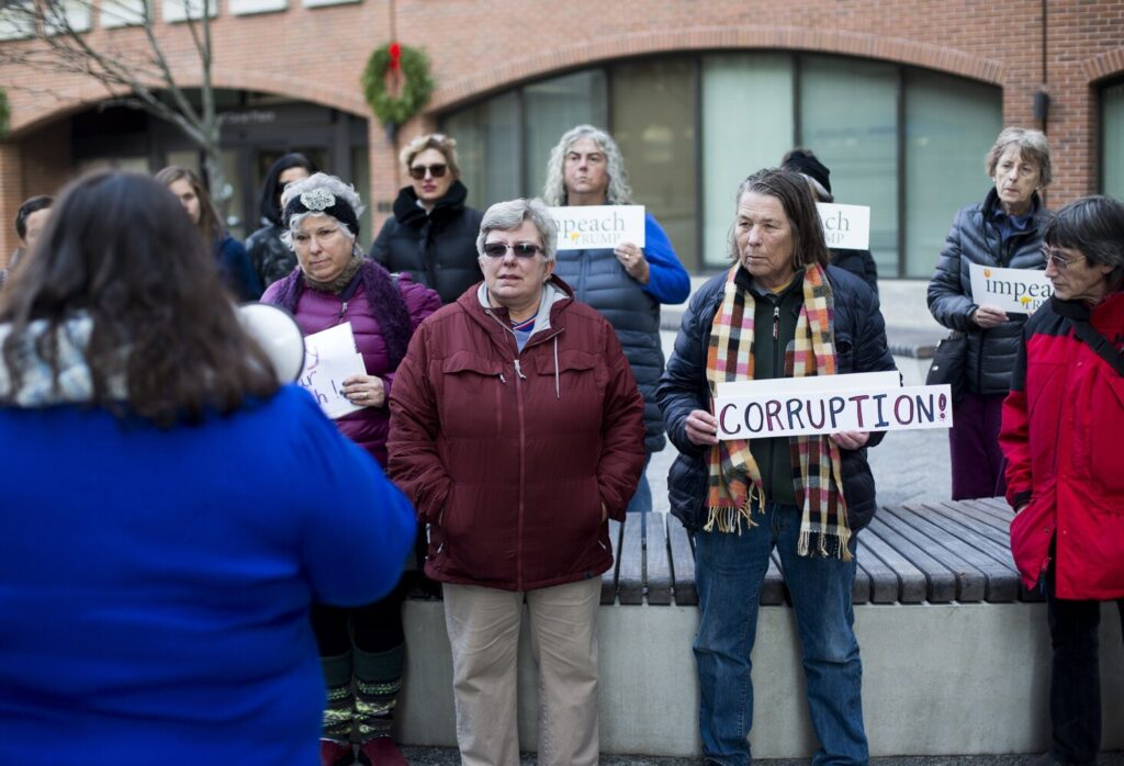 People attend a protest at the Portland office of Sen. Susan Collins on Tuesday. The protest, organized by Mainers for Accountable Leadership, pressed for Collins to support the impeachment of President Trump.