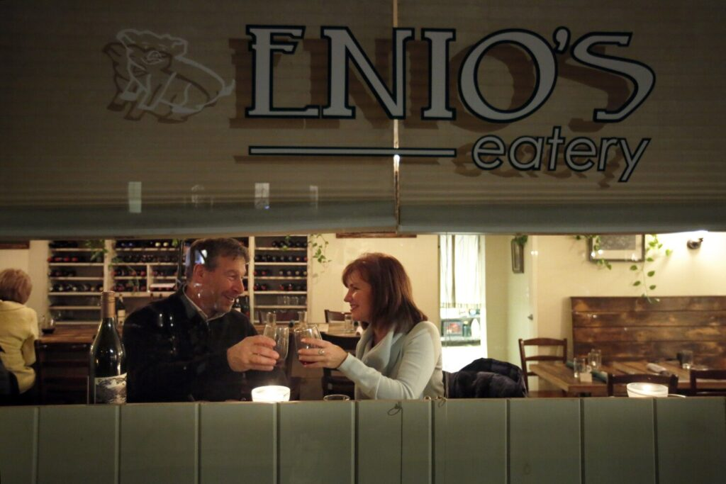 David Turgelsky, left, and Tina Crellin of Cape Elizabeth dine at a window seat at Enio's, the sort of neighborhood restaurant everybody wishes were in their own neighborhood.