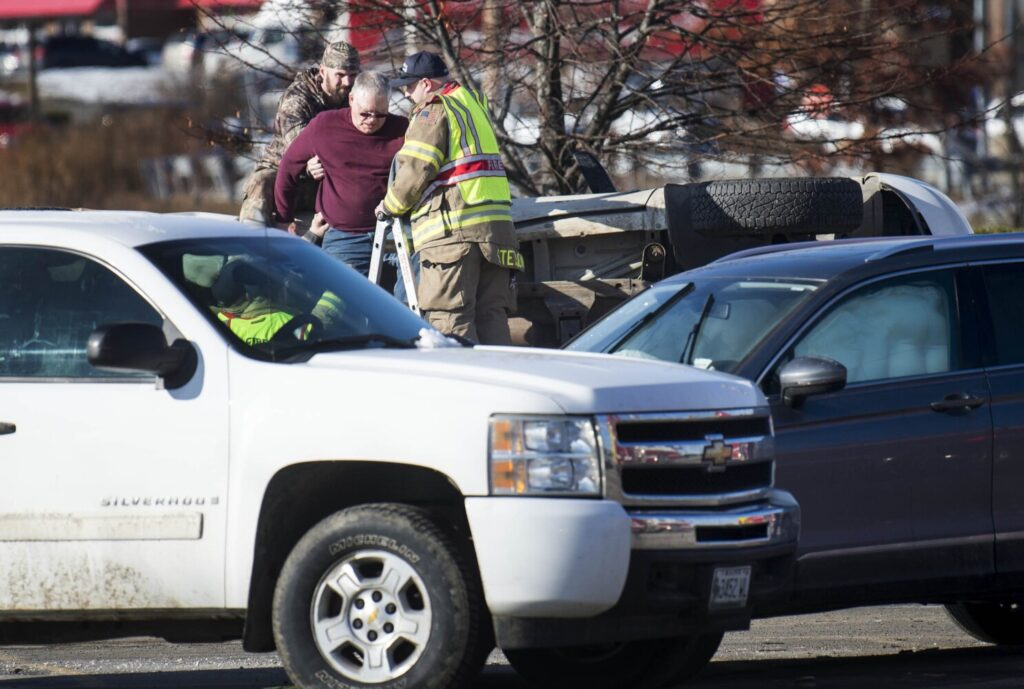 Waterville fire department rescue tech Shawn Stetson helps a man down from his overturned pickup truck Friday afternoon at the scene of a multi-vehicle crash at Elm Plaza and Main Street in Waterville.