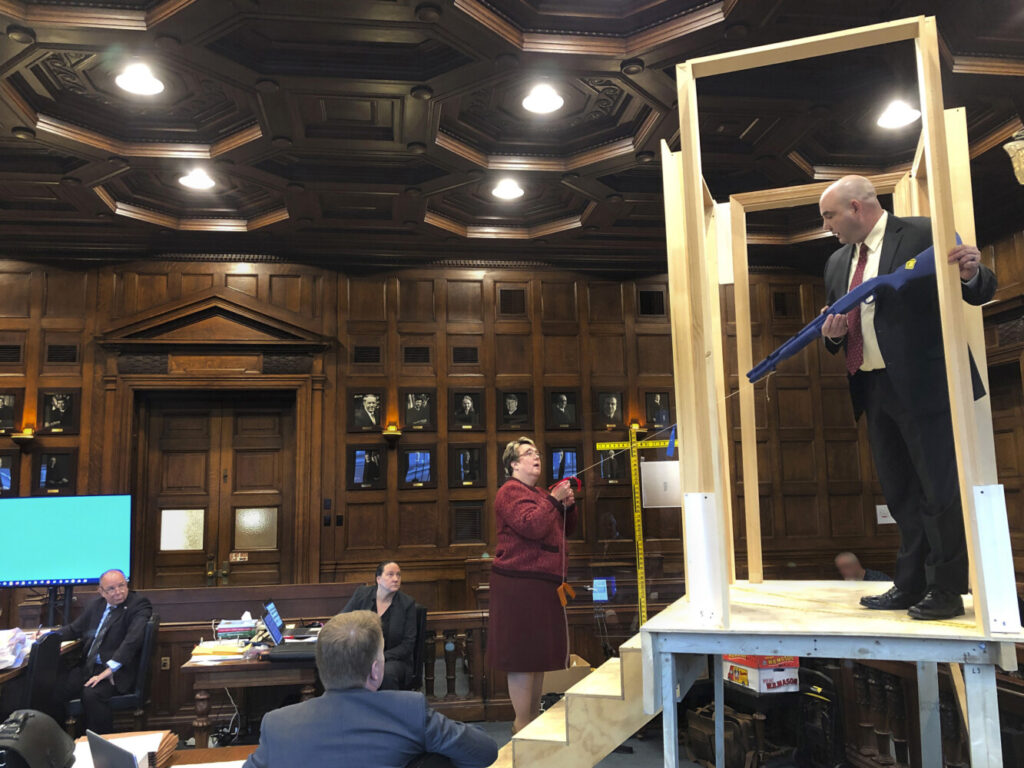 In Cumberland County Superior Court on Monday, Maine State Police Detective Larry Rose holds a mock shotgun while standing at the top of a replica of the stairs in the Windham home where Noah Gaston shot and killed his wife, Alicia Gaston, as she ascended the stairs on the morning of Jan. 14, 2016. Assistant Attorney General Meg Elam holds a string to show the potential path of the shot.