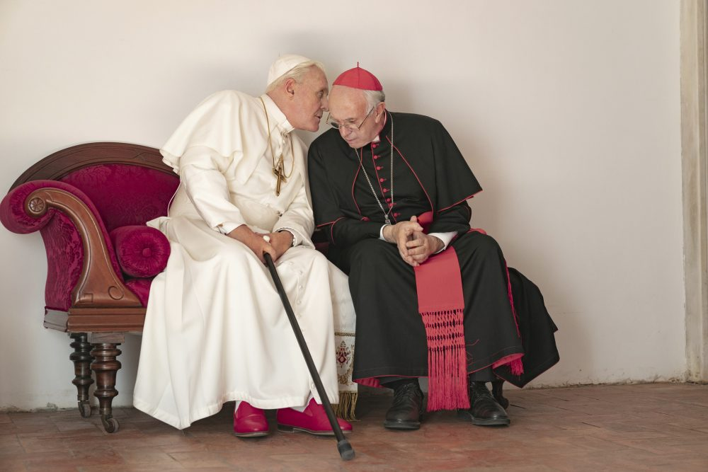 """This image released by Netflix shows Jonathan Pryce as Cardinal Bergoglio, right, and Anthony Hopkins as Pope Benedict in a scene from """"The Two Popes."""""""