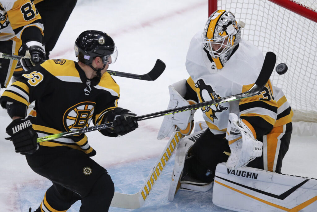 Bruins center Brad Marchand tips the puck past Penguins goaltender Matt Murray in the first period of Boston's 6-4 win on Monday in Boston. Marchand scored twice and Boston won its sixth straight.