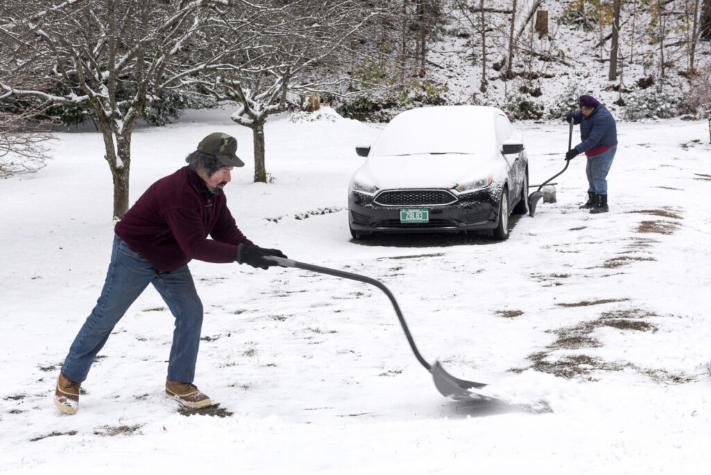 "Frank and Barbara Pascarelli shovel snow from their driveway in White River Junction, Vt., on Tuesday. ""I like being outdoors, but I can think of better things to do,"" said Frank Pescarelli."