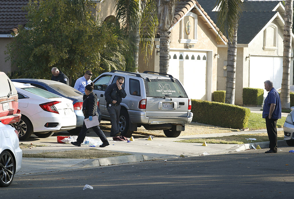 Investigators work Monday in the driveway where the shooting happened at a weekend house party in Fresno, Calif.