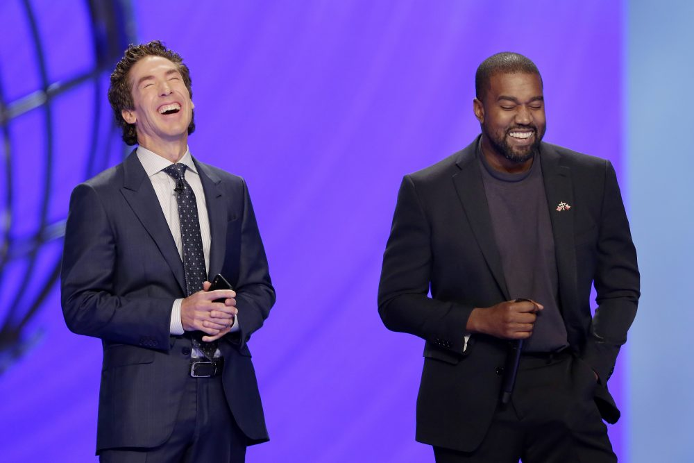 With their eyes closed for prayer, Joel Osteen, left, and Kanye West laugh as West makes a joke while leading the prayer during a service at Lakewood Church, Sunday, Nov. 17 in Houston.
