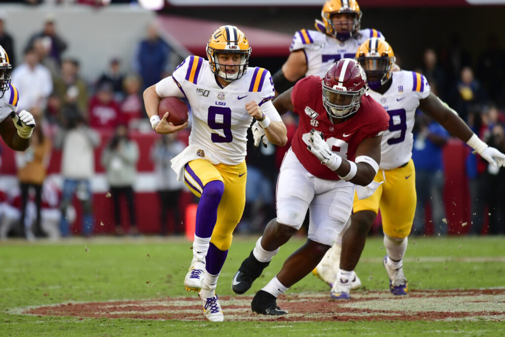 LSU quarterback Joe Burrow runs as Alabama defensive lineman Phidarian Mathis chases him in the first half  Saturday in Tuscaloosa , Ala.