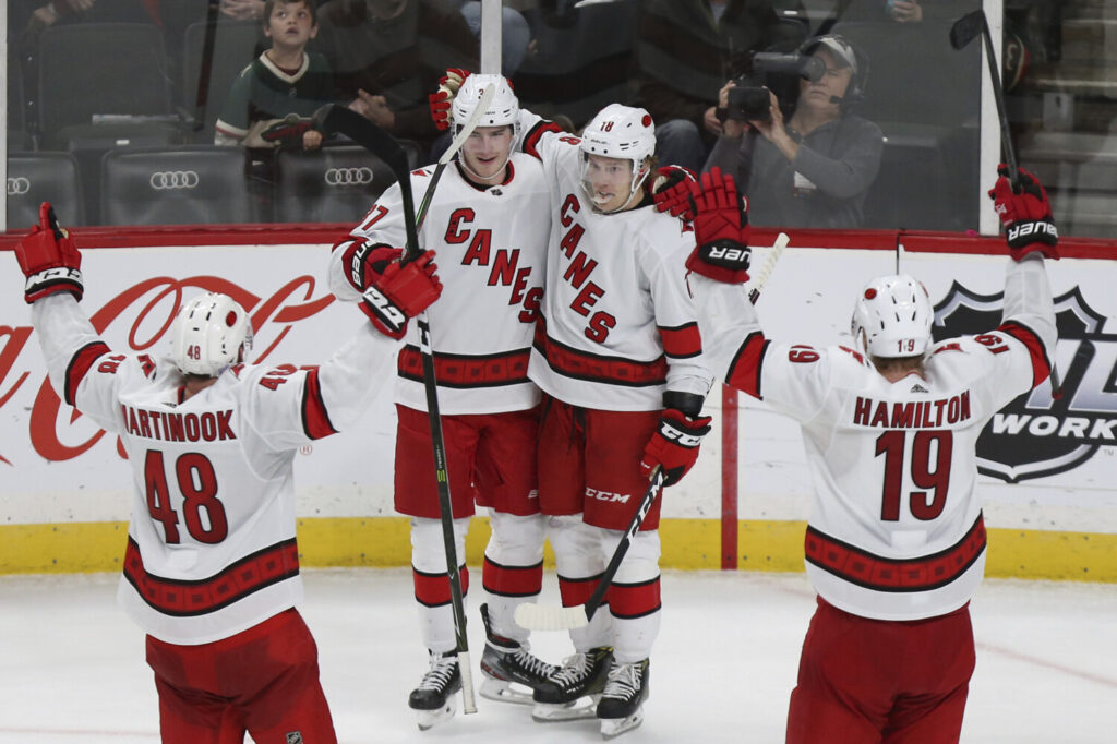 Carolina's Andrei Svechnikov, second from left, celebrates with teammates Ryan Dzingel, Jordan Martinhook, 48, and Dougie Hamilton ,19, after Svechnikov scored the game winning goal against Minnesota during overtime Saturday in St. Paul, Minn. Carolina won 4-3 in overtime.