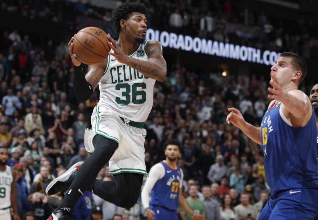 Guard Marcus Smart pulls in a rebound during the Celtics' 96-92 loss to the Denver Nuggets on Friday in Denver. Smart is upset with comments made by a fan during the game and what he said was a lack of response by security at the arena.