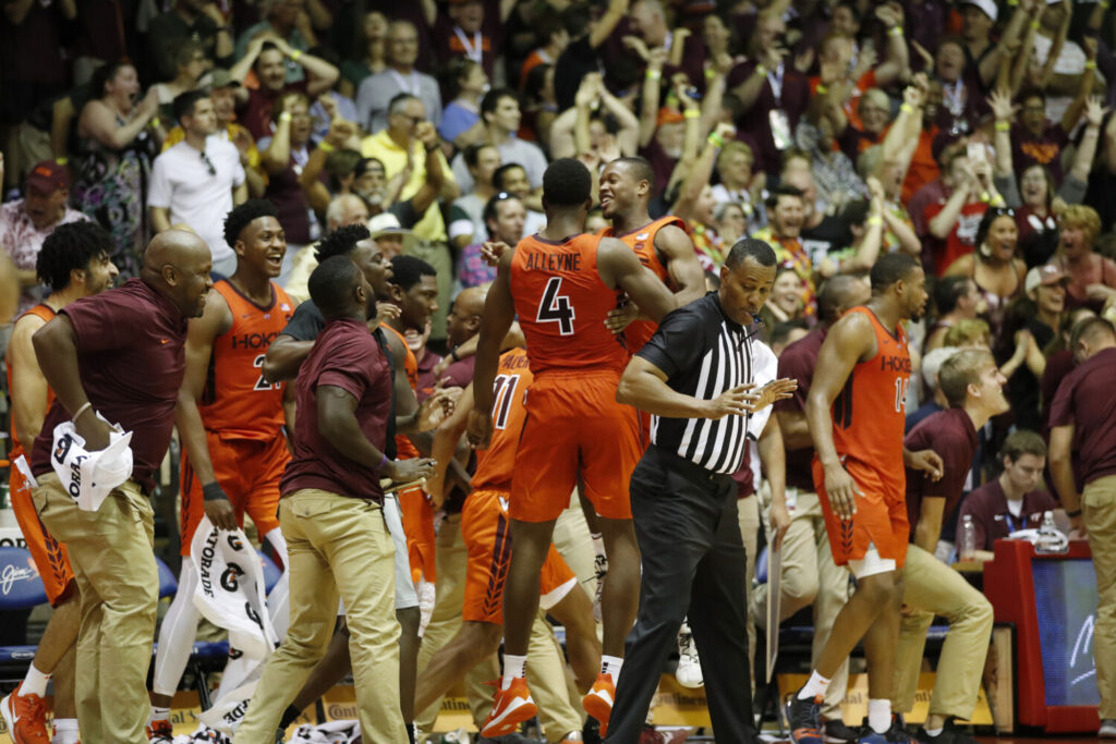 The Virginia Tech bench and fans react after the Hokies' win over No. 3 Michigan State on Monday in Lahaina, Hawaii.