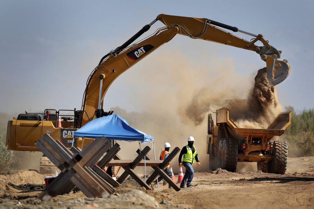Government contractors remove existing Normandy barriers that separate Mexico and the United States in September, in preparation for a section of Pentagon-funded border wall along the Colorado River in Yuma, Ariz.