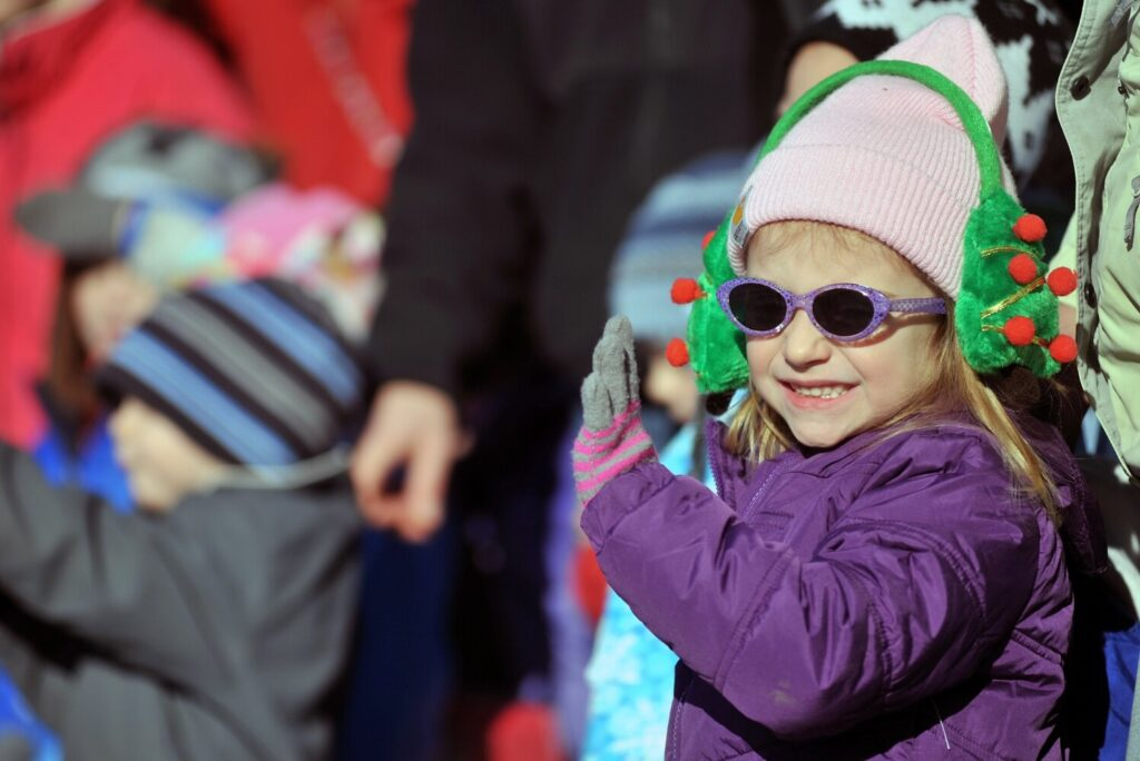 Gracie McCourt, 3, waves as floats roll down Main Street during a past Chester Greenwood Day parade in Farmington.