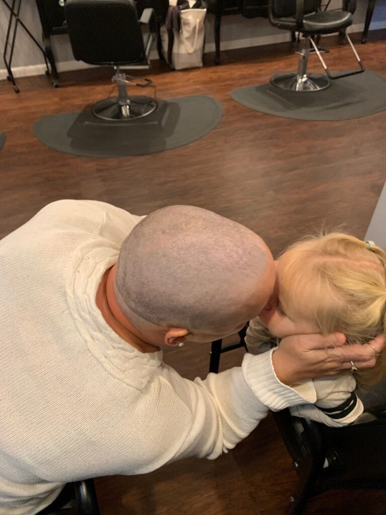 Christine Landes is seen Oct. 17 at Love is in the Hair salon in Augusta with granddaughter Reeslyn Peavey, 2, after Landes had her head shaved. The appointment came about two months after her cancer diagnosis.