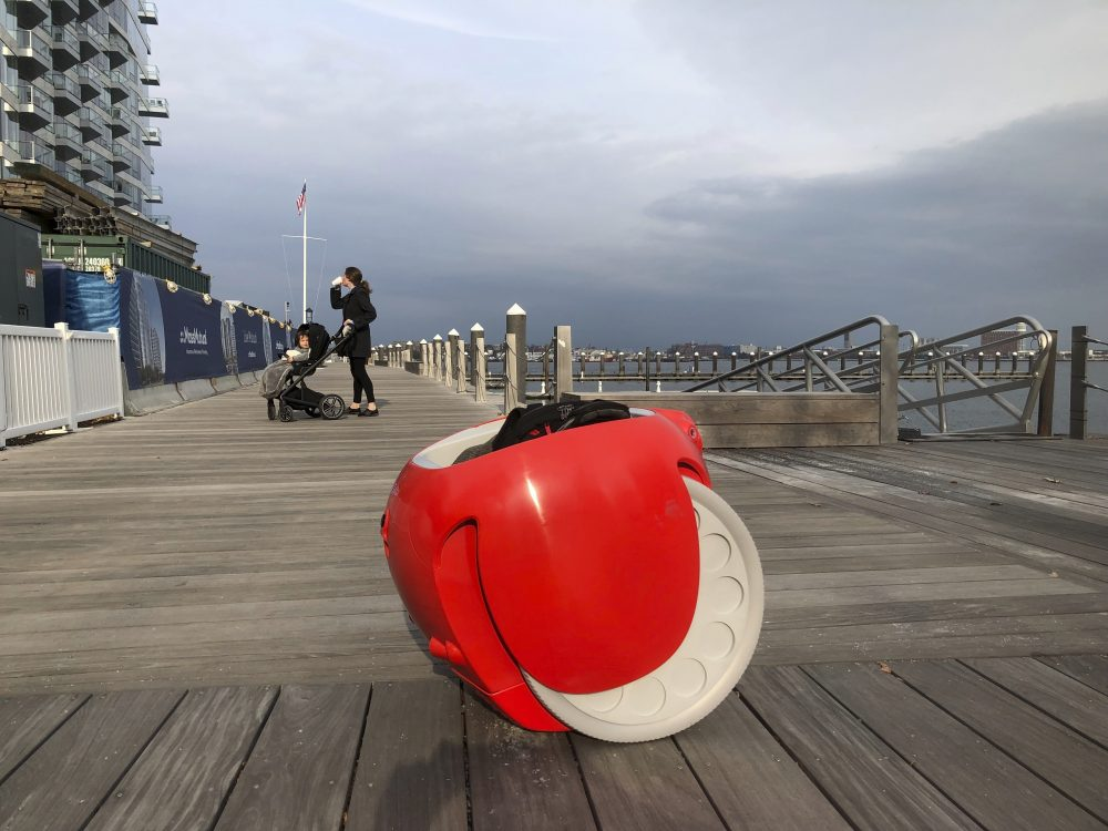 A cargo-carrying robot called the Gita sits near a waterfront park on Monday, Nov. 11, 2019, in Boston. A subsidiary of Italian automaker Piaggio designed the machine to follow its owner carrying groceries and other items. (AP Photo/Matt O'Brien)