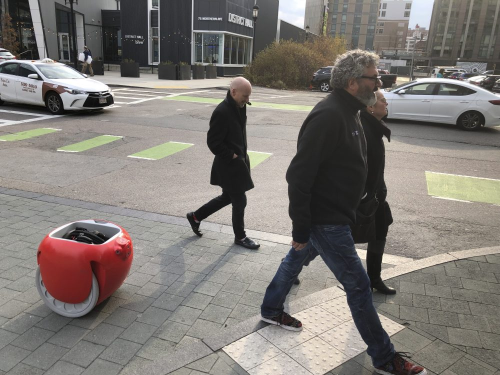 Piaggio Fast Forward CEO Greg Lynn, center, is followed by his company's Gita carrier robot as he crosses a street on Monday in Boston. The two-wheeled machine is carrying a backpack and uses cameras and sensors to track its owner. Associated Press/Matt O'Brien
