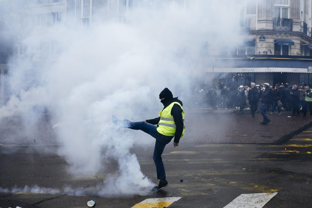 A protestor kicks away a tear gas canister during a yellow vest demonstration marking the first anniversary in Paris on Saturday. Police fired tear gas to push back yellow vest protesters trying to revive their movement on the first anniversary of the sometimes violent uprising against President Emmanuel Macron and government economic policies.