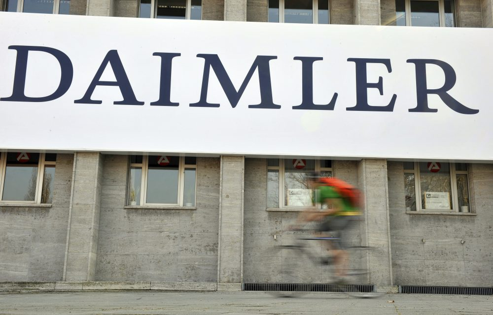 In this April 8, 2009 file photo, a cyclist passes a logo of German car company Daimler in Berlin. German automaker Daimler said Friday, Nov. 29, 2019 that it plans to cut at least 10,000 jobs worldwide by the end of 2022.