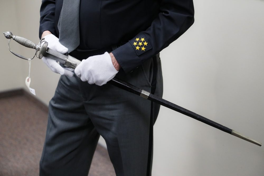 A sword, wielded in the American Revolution and the War of 1812, is handled by Hamilton County Sheriff Jim Neil on Wednesday during a news conference to update the investigation into its ownership, in Cincinnati. Police in Connecticut seized the sword, believed to have been stolen in Cincinnati some 40 years ago, last month just hours before it was going up for auction.