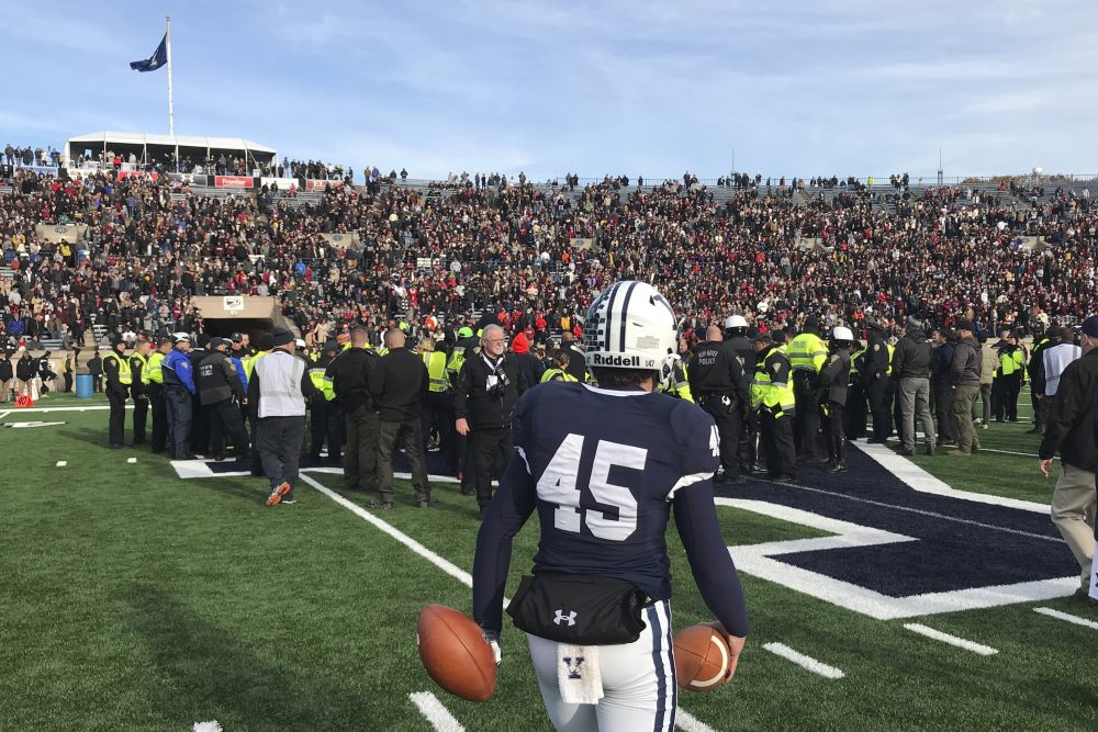 Yale punter Jack Bosman watches as demonstrators stage a protest on the field at the Yale Bowl, disrupting the start of the second half of an NCAA college football game between Harvard and Yale, Saturday in in New Haven, Conn.