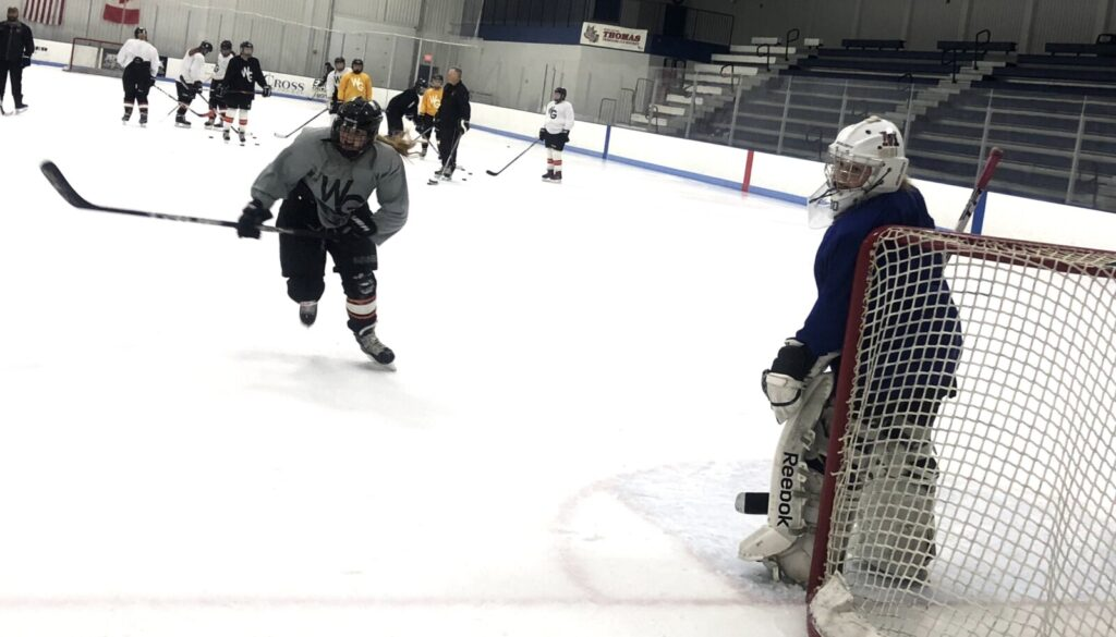 Winslow/Gardiner/Cony junior Lindsey Bell, left, and goalie Emma Michaud compete during a practice drill Thursday at the Camden National Bank Ice Vault in Hallowell. The Black Tigers begin their season Saturday.