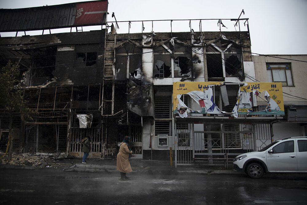 People walk past a burned out building from demonstrators protesting authorities' decision to raise gasoline prices, in Karaj, Iran, on Monday. An article published Tuesday in the hard-line newspaper Keyhan is suggesting that those who led violent protests will be executed as the unrest continues.