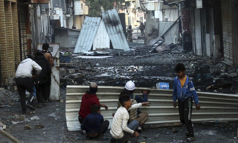 Anti-government protesters take cover during clashes with security forces in Baghdad on Saturday.