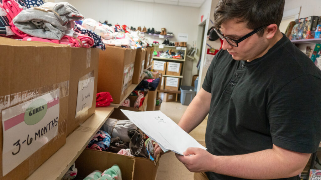 Keegan Drake, a volunteer at the Maine Children's Home for Little Wanderers in Waterville , is seen looking at items. This year donations are needed to fill the boxes for 1,700 children.