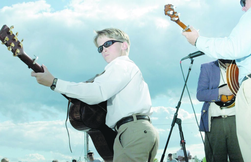 A young member of The Bluegrass Tradition Band plays at what was then the National Folk Festival in Bangor in 2002. The festival has called it quits after 18 years.