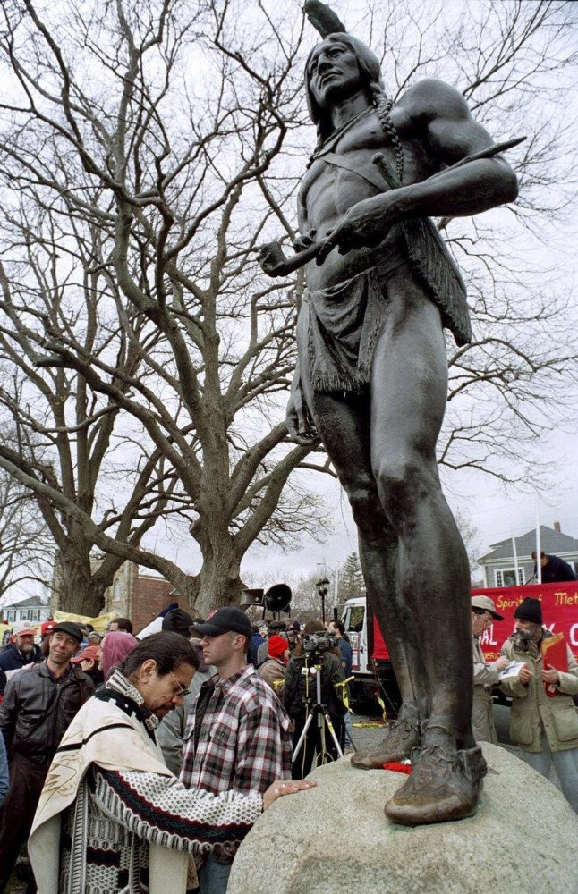 Andres Araica prays in front of a statue of Massasoit in Plymouth, Mass., before a protest march to commemorate the annual National Day of Mourning on Thanksgiving Day in 1998. The first National Day of Mourning was held in 1970 and supporters plan to gather Thanksgiving Day this year for the 50th commemoration.