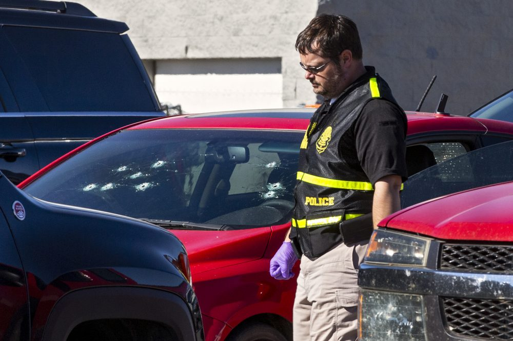A member of the Oklahoma State Bureau of Investigation works the scene of a double-murder suicide in the parking lot of a Walmart in Duncan, Okla., on Monday.