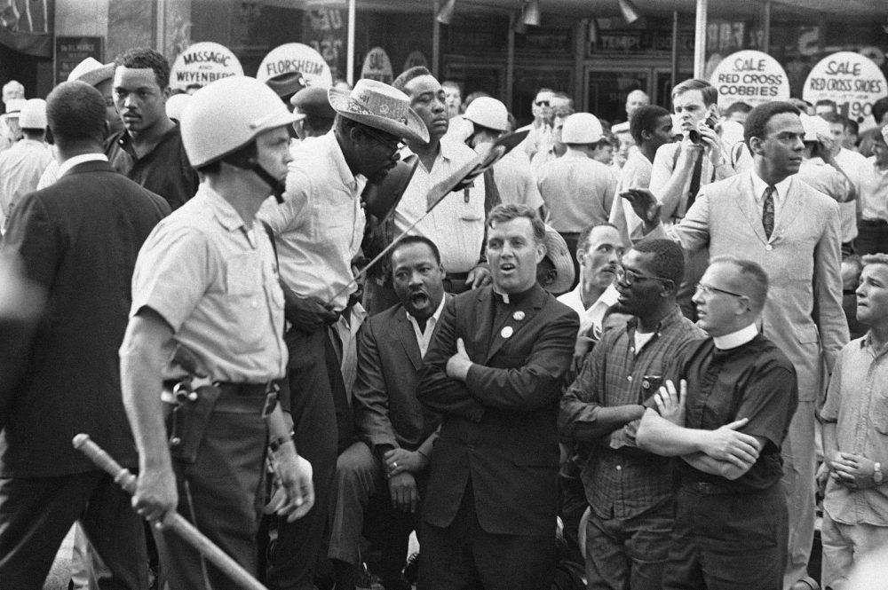 "FILE - In this Aug. 6, 1966, file photo, Martin Luther King, Jr., kneeling on left, leads civil rights marchers in singing and praying in front of real estate office on Chicago Southwest Side. Neighborhoods that King visited included Chicago Lawn, where he was confronted by an angry white mob and was struck by a rock. ""I have never seen, even in Mississippi and Alabama, mobs as hostile and as hate-filled as I've seen here in Chicago,"" King said at the time. (AP Photo/File)"