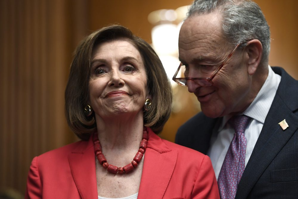 House Speaker Nancy Pelosi of Calif., left, and Senate Minority Leader Sen. Chuck Schumer of N.Y., right, listen as they wait to speak at an event Tuesday on Capitol Hill in Washington.