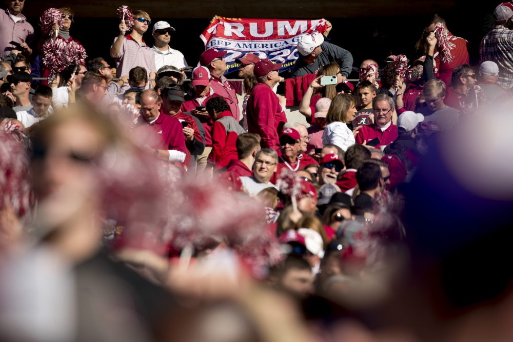 A member of the audience holds up a pro-Trump flag as President Trump and first lady Melania Trump attend a NCAA college football game between LSU and Alabama at Bryant-Denny Stadium, in Tuscaloosa, Ala.