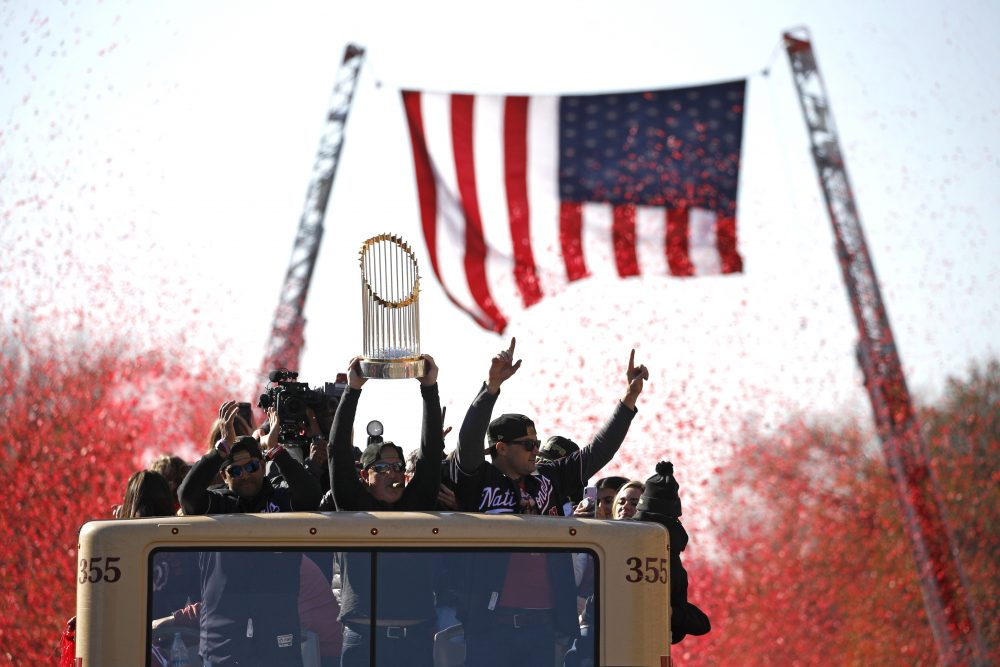 Washington Nationals general manager Mike Rizzo holds up the World Series trophy during a parade to celebrate the team's World Series baseball championship over the Houston Astros on in Washington.