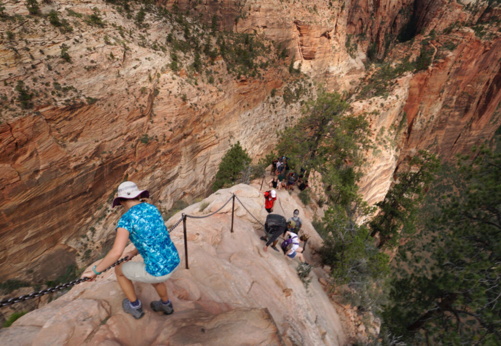Hikers make their way down one of the steeper sections of the Angel's Landing trail in Zion National Park in Utah in 2017. Sections of the trail are narrow with steep drop-offs and have chains to help hikers maintain their balance.