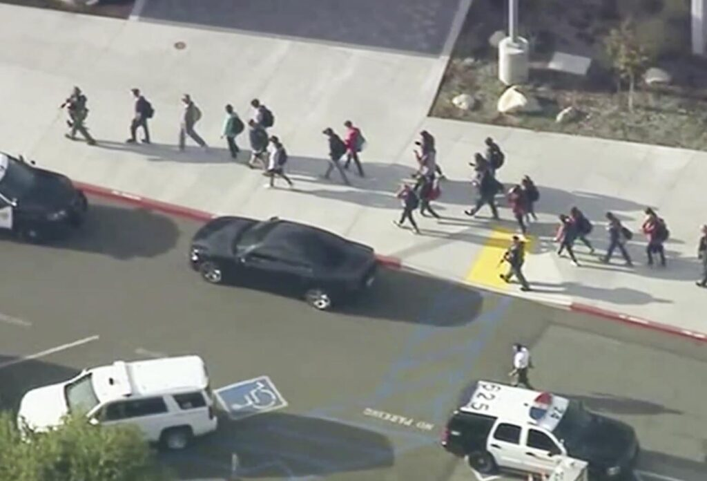 People are lead out of Saugus High School after  a shooting on Thursday morning in Santa Clarita, Calif.