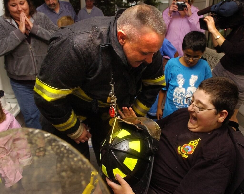 Winslow firefighter Scott Higgins awards Casey Grant a genuine firefighters helmet in August 2007. Higgins died on Monday after serving 18 years on the Winslow Fire Department.