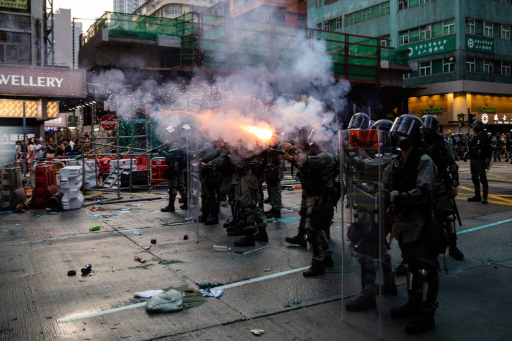 Riot police deploy tear gas on Nathan Road during a protest Oct. 20 in the Mong Kok district of Hong Kong.