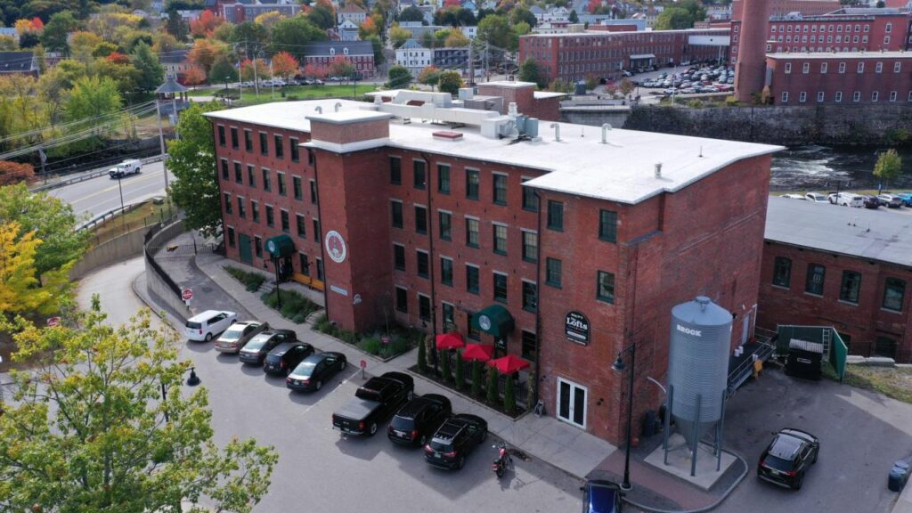 The former mill building that houses The Lofts, a 22-unit apartment complex, and The Run of the Mill Public House & Brewery, a large restaurant and brew pub, is going to auction Thursday. The building is being marketed as an investment property and no tenant changes are expected.