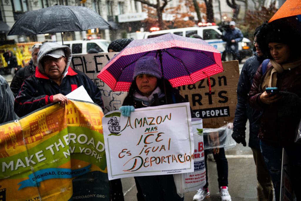 A woman holds a sign protesting Amazon.com's ties to U.S. Immigration and Customs enforcement during a protest outside the penthouse building of Jeff Bezos, the company's founder and chief executive officer, in New York, on Tuesday. Bloomberg photo by Mark Kauzlarich