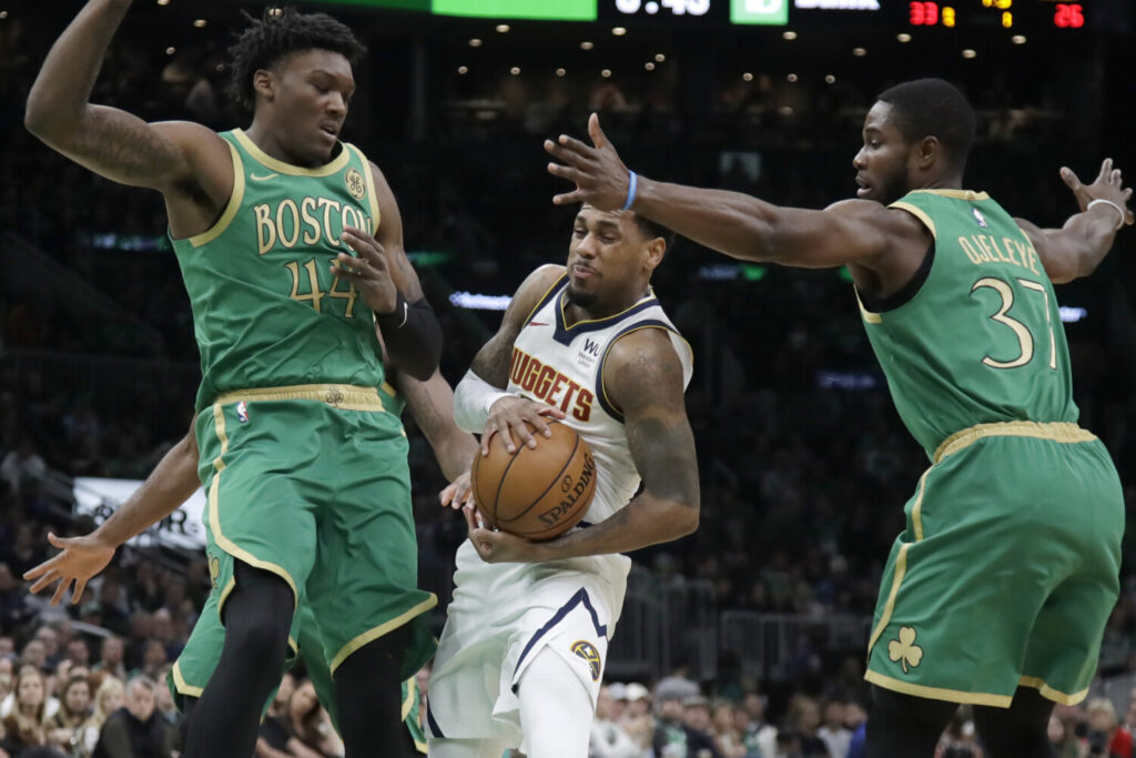 Nuggets guard Monte Morris, center, drives between Celtics center Robert Williams III, left, and forward Semi Ojeleye in the first quarter of their game on Friday night in Boston.