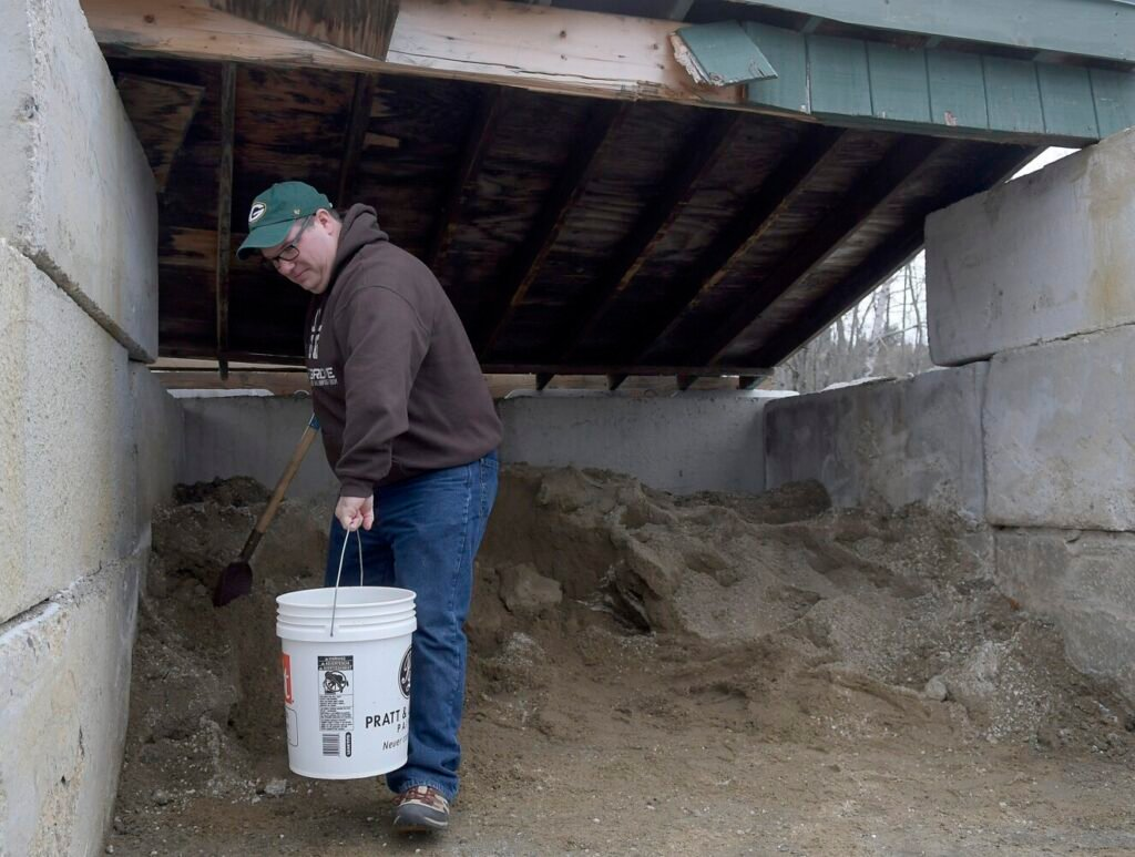 "Wes Holland collects a bucket of salt and sand Monday from a shed at Gardiner Public Works. Shoveling two buckets of the mix of melting agent and absorbent for his home was the last step in preparing for the first snowstorm of the season. ""I've a got a wood stove,"" the transplant from Oklahoma to Gardiner  said. ""I'm ready for it."""