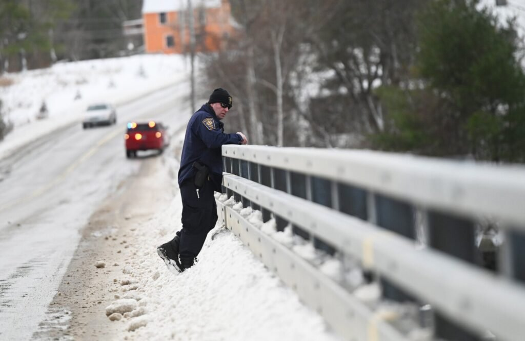 Falmouth police Lt. Frank Soule looks out on the Presumpscot River from the bridge on Route 9 in Falmouth on Wednesday as the search continued for Anneliese Heinig.