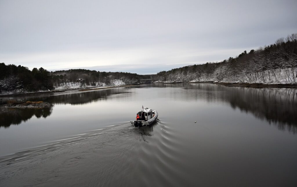 A dive team on a Maine Marine Patrol boat makes its way up the Presumpscot River in Falmouth on Wednesday as the search continued for Anneliese Heinig, 37, who disappeared after she left her car on Interstate 295.