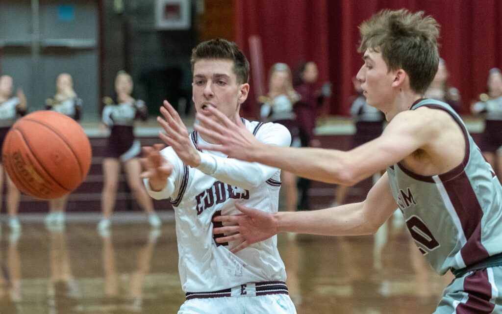Edward Little's Austin Brown, left, passes to a teammate under the basket while being defended by Windham's Eric Weisser during the first quarter of Friday night's game in Auburn.