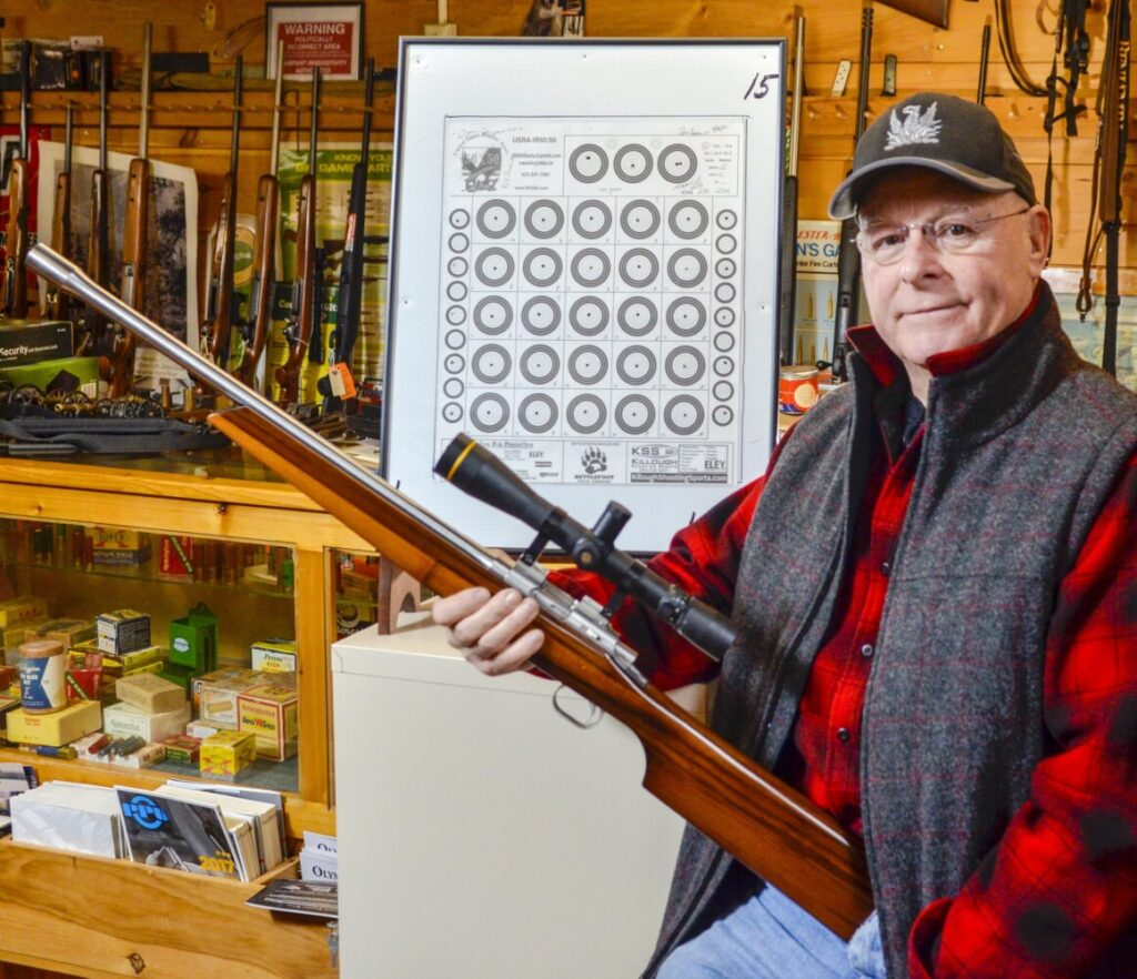 Gary Hamilton holds the Tony Larson .22-caliber sporter rifle Friday at Neilson's Sporting Goods in Farmingdale, the gun he used to shoot a 250-point 25X target next to him.