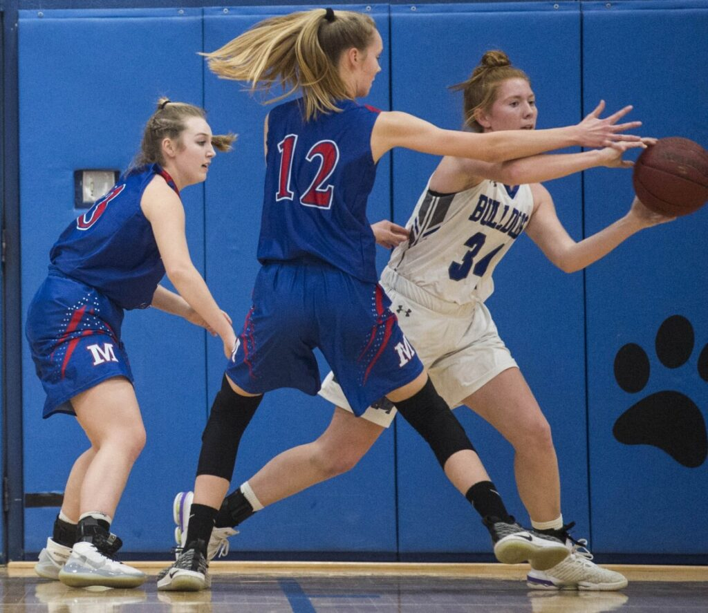Lawrence's Sarah Poli (34) looks to pass the ball while being defended by Messalonskee's Grace Wener (12) and Brooke Martin, left, on Tuesday in Fairfield.