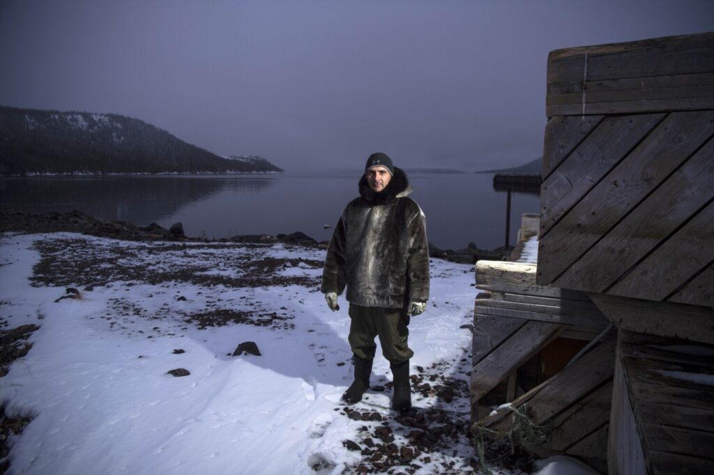 Karl Michelin poses for a portrait at the water's edge of Lake Melville in Rigolet wearing a dickie made of seal skin from a seal he hunted from the bay on Nov. 13, 2019.