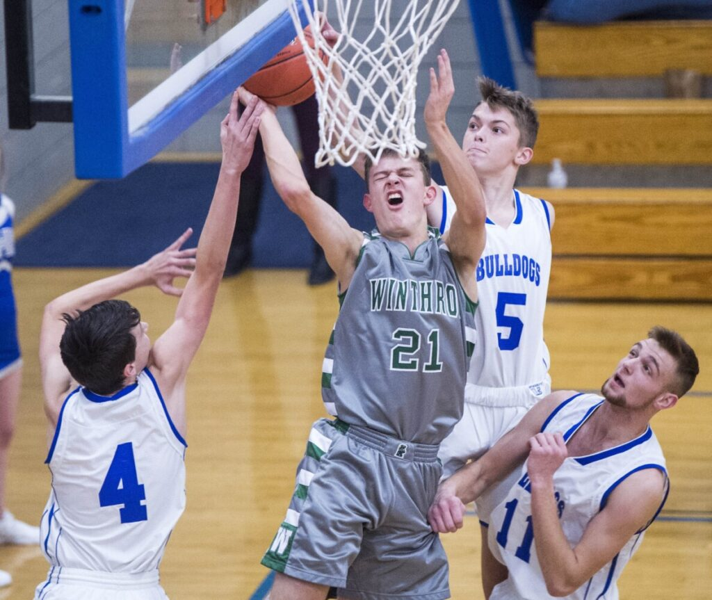 Winthrop's Brad Bourne (21) draws the foul from Madison's Caden Franzose (4) left, as teammate Cameron Cobb (5) helps last Thursday in Madison.